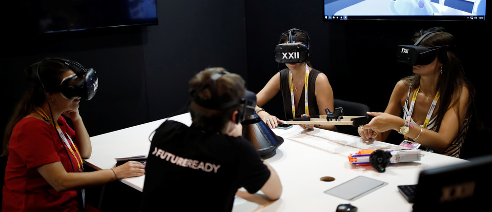 People wear virtual reality (VR) headsets at the XXII Group exhibition stand during the Viva Technology conference in Paris, France, June 15, 2017.  REUTERS/Benoit Tessier - RTS1783H