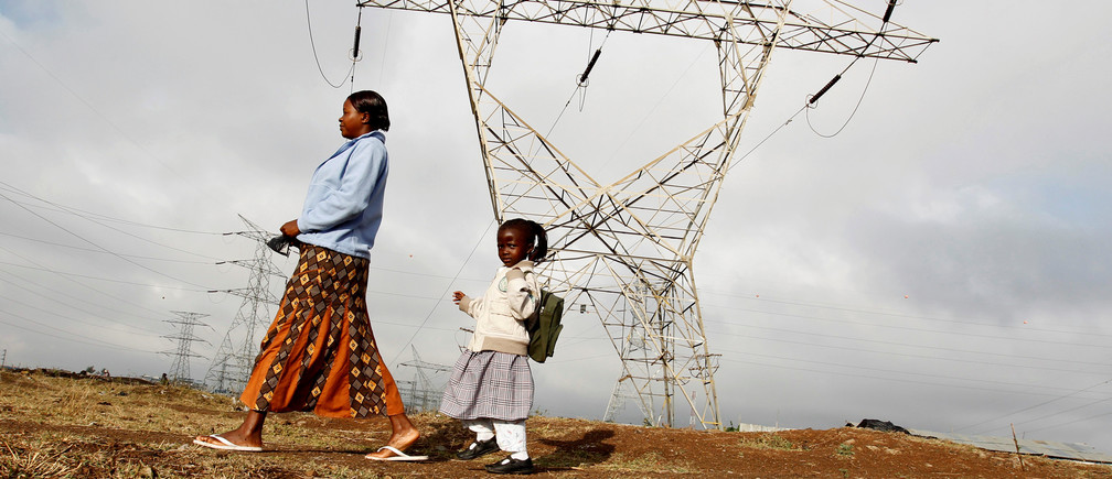 A woman walks her child to school past high voltage electrical pylons on the outskirts of Kenya's capital Nairobi