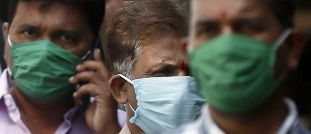 Men wearing protective masks walk inside the premises of a hospital where a special ward has been set up for the coronavirus disease in Mumbai, India, March 17, 2020.
