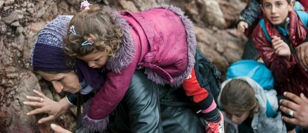 A migrant woman carries her child after arriving at a rocky beach on the Greek island of Lesbos after crossing a part of the Aegean Sea from the Turkish coast to Lesbos October 11, 2015.