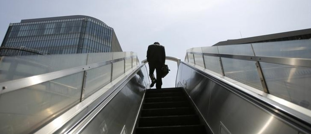 A businessman rides on an escalator in Tokyo's business district April 1, 2013. Japanese business sentiment improved in the first three months of 2013, a central bank survey showed, after Prime Minister Shinzo Abe's aggressive monetary and fiscal policy prescriptions helped to weaken the yen and bolster share prices.   REUTERS/Toru Hanai (JAPAN - Tags: POLITICS BUSINESS)