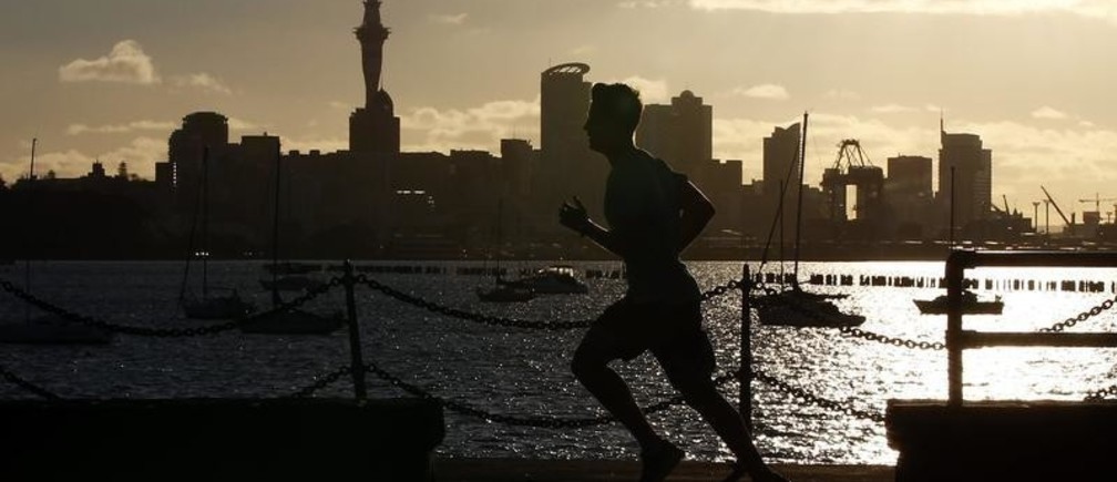 A jogger runs along the seawall in Auckland September 26, 2011, with the city skyline in the background.   REUTERS/Stefan Wermuth (NEW ZEALAND  - Tags: CITYSCAPE TRAVEL SOCIETY) - SR1E79Q0PEWOM