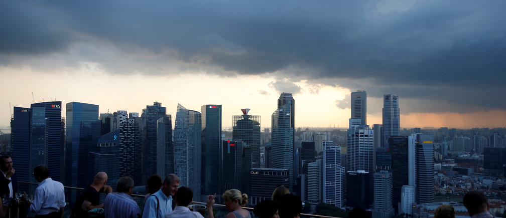 Tourists have drinks at a hotel rooftop bar as clouds gather over the central business district in Singapore June 6, 2016. REUTERS/Edgar Su/File Photo - RTX2R439