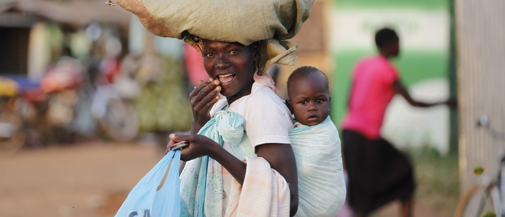 A woman carries a child and a bag on her head within the trading centre of the U.S. President Barack Obama's ancestral village of Nyang'oma Kogelo, west of Kenya's capital Nairobi, July 15, 2015. President Obama visits Kenya and Ethiopia in July, his third major trip to Sub-Saharan Africa after travelling to Ghana in 2009 and to Tanzania, Senegal and South Africa in 2011. He has also visited Egypt, in North Africa, and South Africa for Nelson Mandela's funeral. Obama will be welcomed by a continent that had expected closer attention from a man they claim as their son, a sentiment felt acutely in the Kenyan village where the 44th U.S. president's father is buried. Picture taken July 15, 2015. REUTERS/Thomas Mukoya - GF10000168089