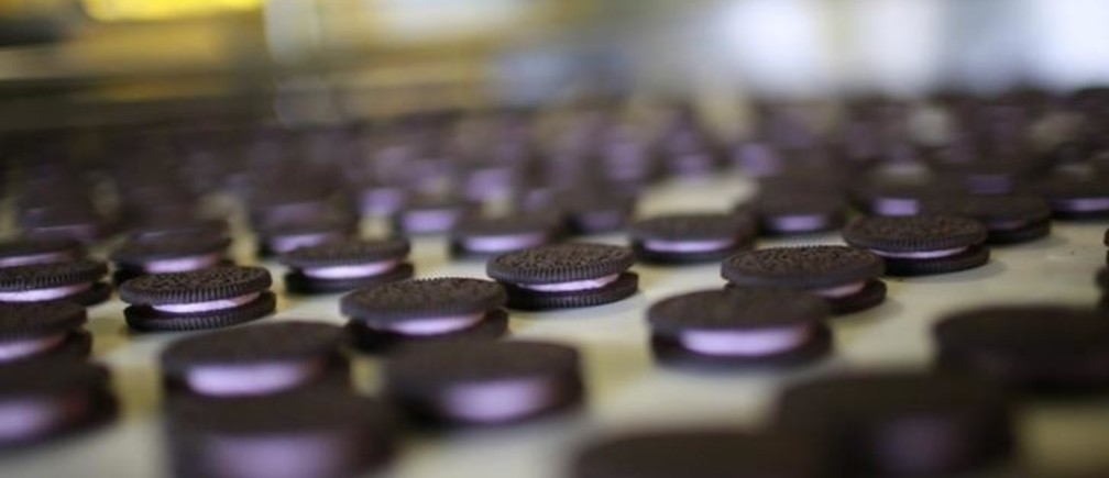 "Freshly-baked Oreo cookies pass along a conveyor belt at a Kraft Foods' factory in Suzhou, Jiangsu province May 30, 2012. Investment may be powering the Chinese economy but experiments like Oreo's gum cookie, a cookie with a glob of gum sandwiched neatly between a pair of Oreo's iconic dark chocolate biscuits instead of the creamy white ""stuff"", which for better or worse never made it to store shelves, are a reminder that consumption is rising sharply. That means it is vital for food companies to get the right products into the market, particularly with demand dimming in the United States and Europe. Picture taken May 30, 2012. To match story CHINA-LOCALISATION/OREOS REUTERS/Aly Song (CHINA - Tags: BUSINESS FOOD SOCIETY)"