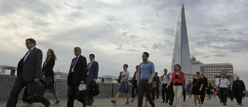 Commuters walk across London Bridge to the City of London August 7, 2013.