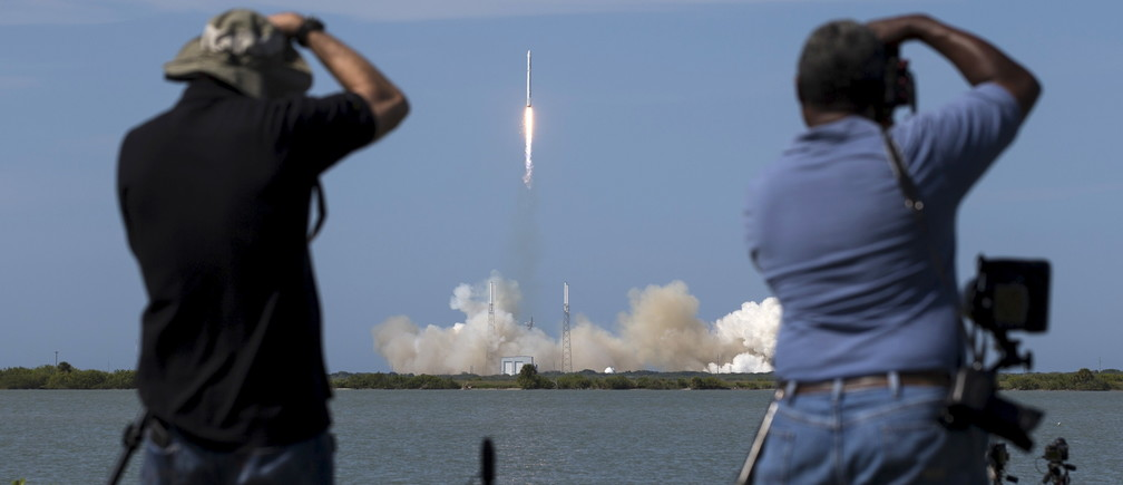 Photographers take pictures of the unmanned SpaceX rocket as it launches from Cape Canaveral, Florida