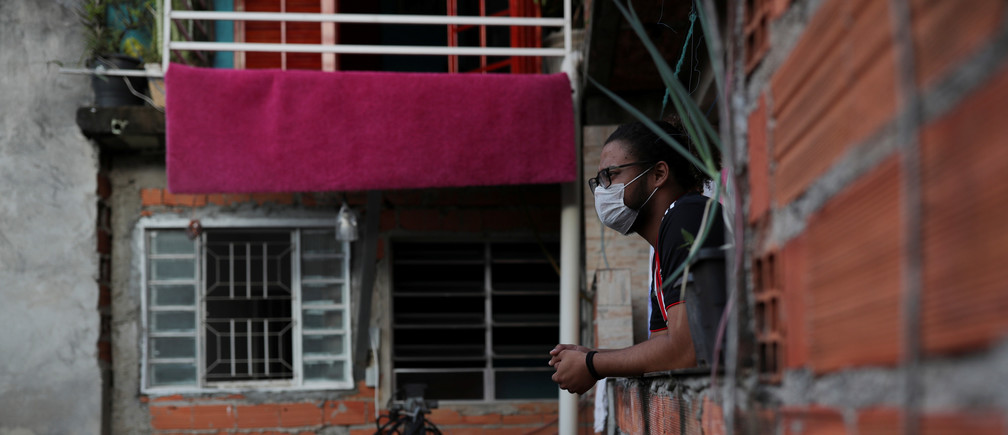 Marcus Vinicius Conceicao dos Santos, 22, looks out from his home as he self-isolates with another 19 people after showing symptoms of coronavirus disease (COVID-19), in the city's biggest slum Paraisopolis after residents have hired a round-the-clock private medical service, in Sao Paulo, Brazil March 30, 2020. Picture taken March 30, 2020. REUTERS/Amanda Perobelli - RC2GWF9GGCOC