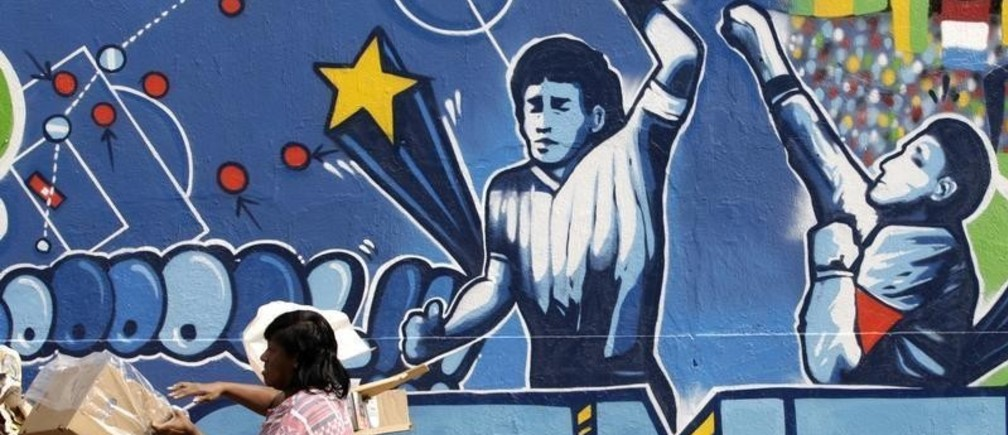 "A resident stands near a mural depicting the famous ""Hand of God"" goal by former Argentine soccer star Diego Maradona, in light of the upcoming 2010 FIFA World Cup at the Agua Santa neighborhood in Rio de Janeiro May 21, 2010.  REUTERS/Sergio Moraes  (BRAZIL - Tags: SPORT SOCCER WORLD CUP SOCIETY) - GM1E65M05VS01"