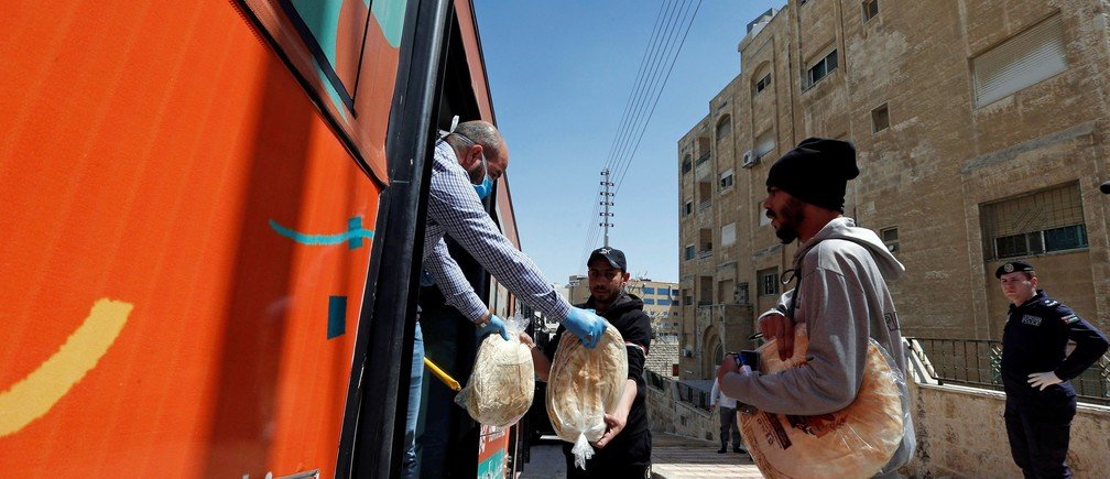 People buy bread from a bus delivering food after Jordan announced it would extend a curfew indefinitely, amid concerns over the spread of coronavirus disease (COVID-19), in Amman, Jordan March 24, 2020. REUTERS/Muhammad Hamed