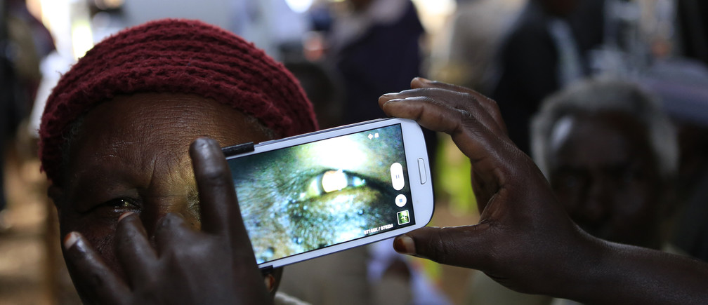 "A woman undergoes an eye examination using a smartphone at a temporary clinic by International Centre for Eye Health at Olenguruone in the Mau Summit 350km (217 miles) west of Kenya's capital Nairobi, October 29, 2013. The organisation is running clinics for 5000 eye patients using a new application ""Peek Vision"" that enables doctors to give patients a full eye examination using smartphones. The phone diagnoses and conducts cataract scans, basic eye tests, and uses the phone's flash to illuminate the back of the eye for signs of disease. It also sends all recorded data of a patient along with their location to a doctor for analysis."