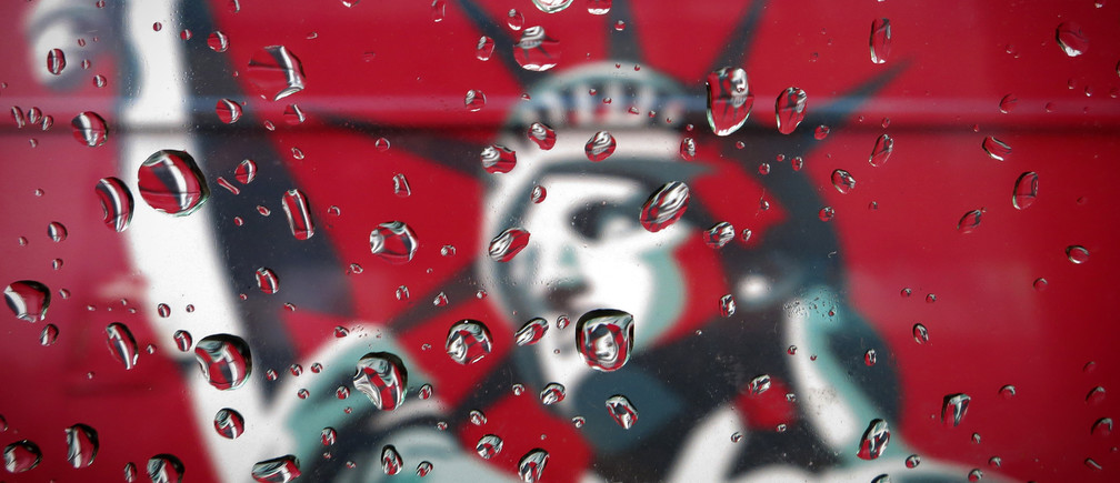 An image of the Statue of Liberty is pictured though a rain covered taxi window in New York April 15, 2014.   REUTERS/Carlo Allegri (UNITED STATES - Tags: SOCIETY TPX IMAGES OF THE DAY) - GM1EA4G0B6X01
