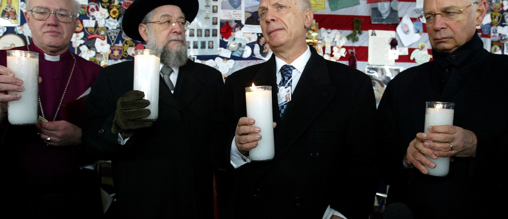 Klaus Schwab (R) , Founder and President of the World Economic Forum, Rabbi Arthur Schneier (2nd from R), Founder and President of Appeal of Conscience, and The Most Reverend George Leonard Carey, Archbishop of Canterbury (L) enlight their candles at Ground Zero during a visit of the religious leaders participating at the 32nd Annual Meeting of the World Economic Forum in New York Sunday, February 3, 2002