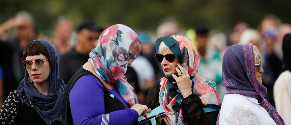 Women wearing headscarves as tribute to the victims of the mosque attacks are seen before Friday prayers at Hagley Park outside Al-Noor mosque in Christchurch, New Zealand March 22, 2019. REUTERS/Jorge Silva - RC1CB42E8570