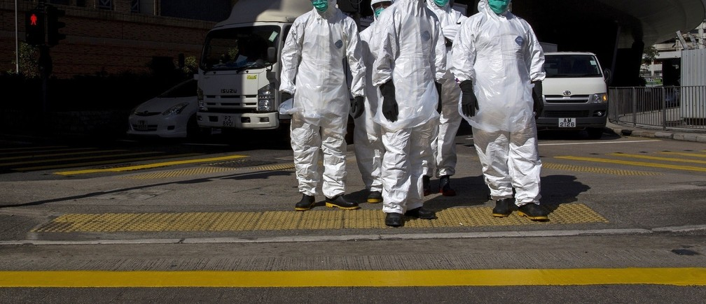 Health officers in full protective gear wait to cross a road near a wholesale poultry market in Hong Kong December 31, 2014.
