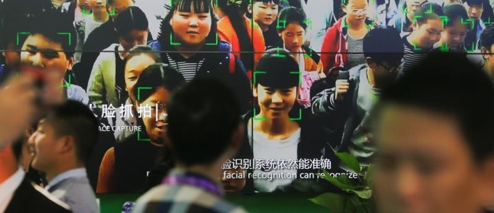 Visitors walk past a screen showing a demonstration of facial recognition software at the Security China 2018 exhibition on public safety and security in Beijing, China October 23, 2018.  Picture taken October 23, 2018.   REUTERS/Thomas Peter - RC1D51E07770