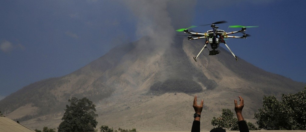 An official of the Center for Research and Technology Volcanoes Development (BPPTK) releases a drone quadcopter to monitor activity from the Mount Sinabung volcano at Sibintun village in Karo district, North Sumatra province February 4, 2014. Indonesia's Mount Sinabung volcano erupted and killed at least 11 people on the western island of Sumatra on Saturday, the first time it is known to have claimed any lives, a senior government official said.