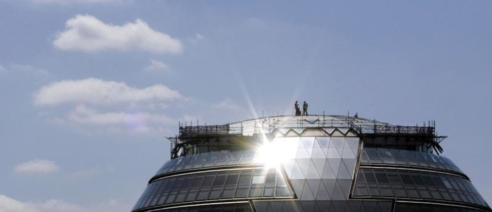 """Workers install photovoltaic solar panels on the roof of City Hall in London in this May 23, 2007 file photo.  Fear of climate change and the need to find green alternatives to dirty coal, unpopular nuclear power and unreliable gas imports from Russia are fuelling an embryonic movement in Europe to build """"smart cities"""".  To match feature ENERGY-CITIES   REUTERS/Alessia Pierdomenico (BRITAIN) - GM1E52A0OFU01"""