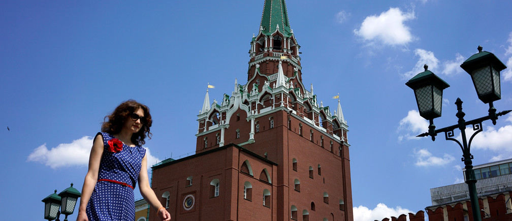 A woman walks at Alexandrovsky Garden as the Troitskaya (Trinity) Tower of Kremlin is seen in the background, in Moscow, Russia, June 30, 2016.