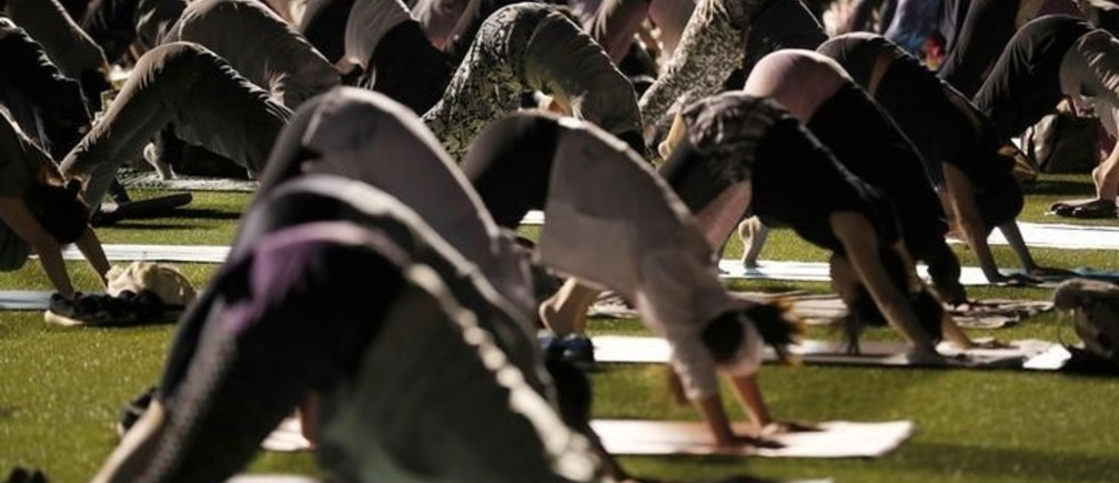 Participants practice yoga during an evening yoga event to promote a healthier lifestyle at a baseball stadium in Tokyo, Japan September 29, 2017. REUTERS/Kim Kyung-Hoon