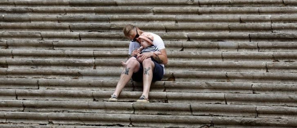 "A father and son sit on the stairs leading to Girona Cathedral before the filming for Season 6 of HBO TV series ""Game of Thrones"" northeast of Spain, Girona, September 3, 2015. REUTERS/Gustau Nacarino"