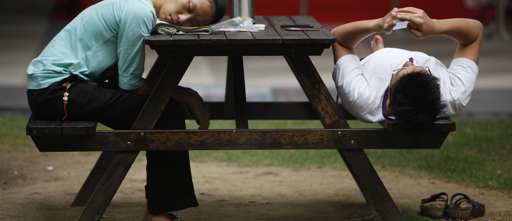 A woman sleeps at a bench at the end of a working day at the central business district of Singapore November 28, 2013. REUTERS/Edgar Su (SINGAPORE - Tags: SOCIETY) - GM1E9BS1NZ801