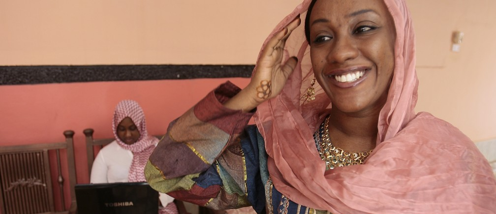 Shiraz Al-Tayeb Hamid (R), 28, managing director of her family's plastic factory, smiles at her house in Khartoum February 27, 2009.