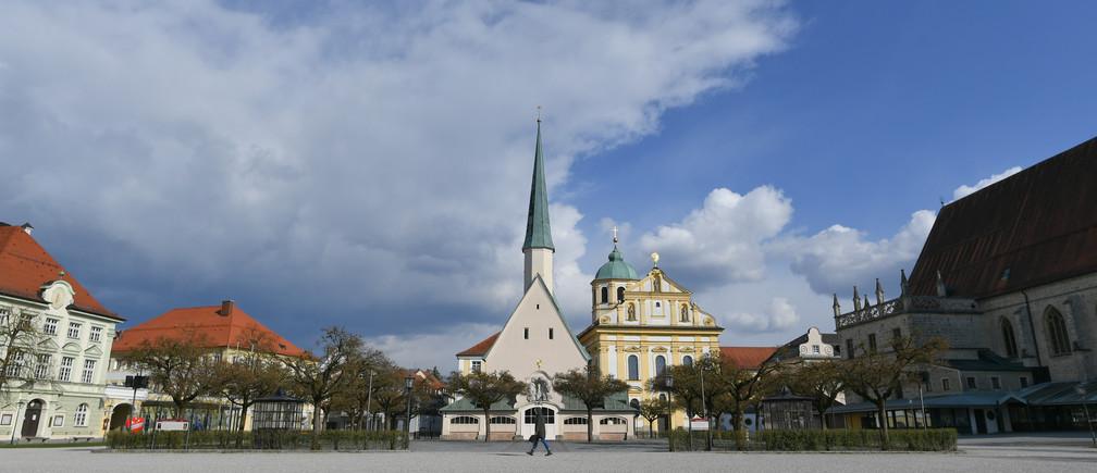 Une personne marche sur une place vide à la chapelle de la Gracieuseté à Altoetting, en Allemagne, le 31 mars 2020, alors que la propagation de la maladie à coronavirus (COVID-19) se poursuit.
