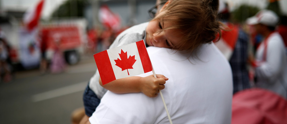 "Emery Litynsky, 2, holds a Canadian flag during the East York Toronto Canada Day parade, as the country marks its 150th anniversary with ""Canada 150"" celebrations, in Toronto, Ontario, Canada July 1, 2017.    REUTERS/Mark Blinch - RTS19E0G"