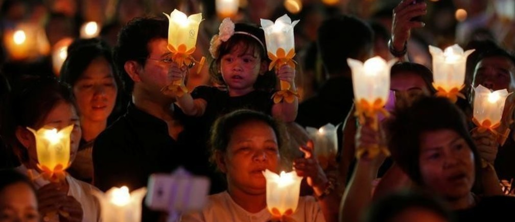 Thais hold candle lights as they pray to celebrate the new year at Sanam Luang park in Bangkok, Thailand  January 1, 2017.   REUTERS/Chaiwat Subprasom