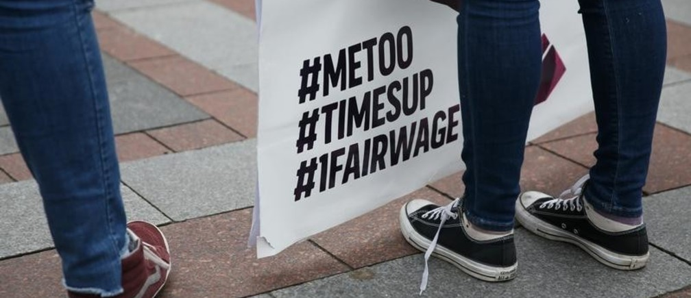 Maddi Basse, right, holds a large #NotOntheMenu sign during a rally demanding an end to sexual harassment and to bring awareness to the federal subminimum wage for tipped workers of $2.13 an hour in the restaurant industry at Westlake Park in Seattle, Washington, U.S. February 13, 2018.  REUTERS/Lindsey Wasson - RC1477DB7C70