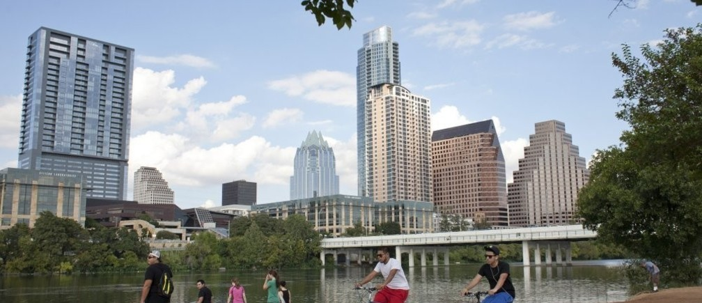 Cyclists pass beneath the downtown skyline on the hike and bike trail on Lady Bird Lake in Austin, Texas.