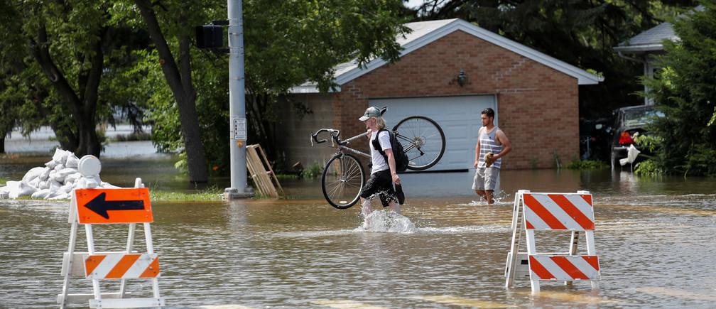 Men walk through a flooded area in Gurnee, Illinois, U.S. July 15, 2017. REUTERS/Kamil Krzaczynski - RTX3BLXL