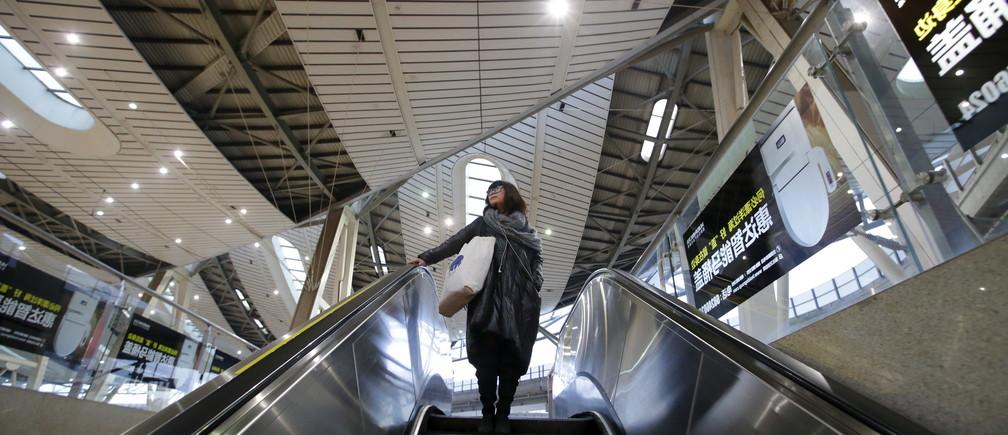 Li Nan, a makeup artist, takes an escalator on her commute into Beijing for work from Tianjin, China, November 18, 2015.