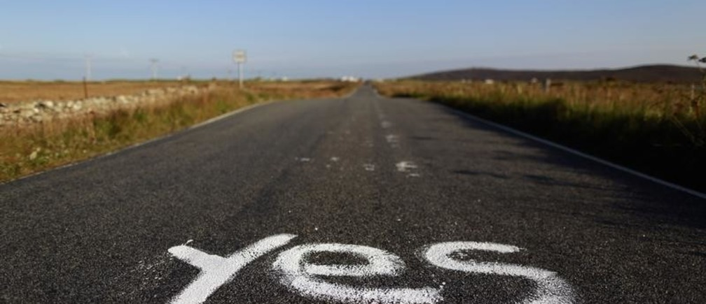 "Graffiti supporting the ""Yes"" campaign is painted on a road in North Uist in the Outer Hebrides September 17, 2014. The referendum on Scottish independence will take place on September 18, when Scotland will vote whether or not to end the 307-year-old union with the rest of the United Kingdom. REUTERS/Cathal McNaughton (BRITAIN - Tags: POLITICS ELECTIONS) - GM1EA9I00IO01"