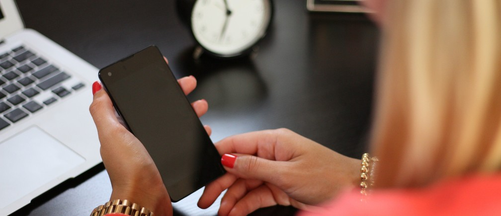 Woman with a phone at a desk workplace distraction time efficiency productivity