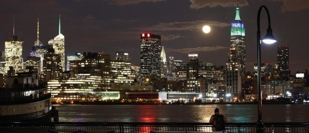 A full moon rises behind the Empire State Building in New York as a man watches in a park along the Hudson River in Hoboken, New Jersey, February 25, 2013. REUTERS/Gary Hershorn (UNITED STATES - Tags: CITYSCAPE)