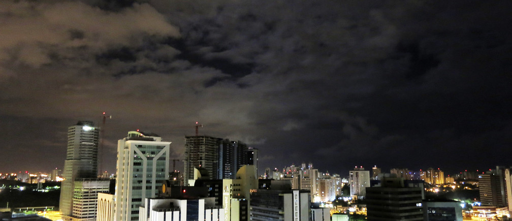 The moon rises above buildings in Salvador, Brazil December 4, 2012. Salvador, the third-largest city in Brazil is the country's oldest metropolis, but has a lower profile than party hot spot Rio de Janiero or the commercial nerve, Sao Paulo. The laid back coastal city, which lies on the All Saints Bay on the Atlantic Ocean, is the heart of Bahia, the Brazilian province know for its rich African culture. Salvador is gearing up for an influx of sports fans, since it has been chosen as one of Brazil's 12 host cities for the FIFA World Cup in 2014.  Picture taken December 4, 2012.  To match TRAVEL-SALVADOR/  REUTERS/Gary Hershorn (BRAZIL - Tags: CITYSCAPE TRAVEL SOCIETY) - RTR3DTJO