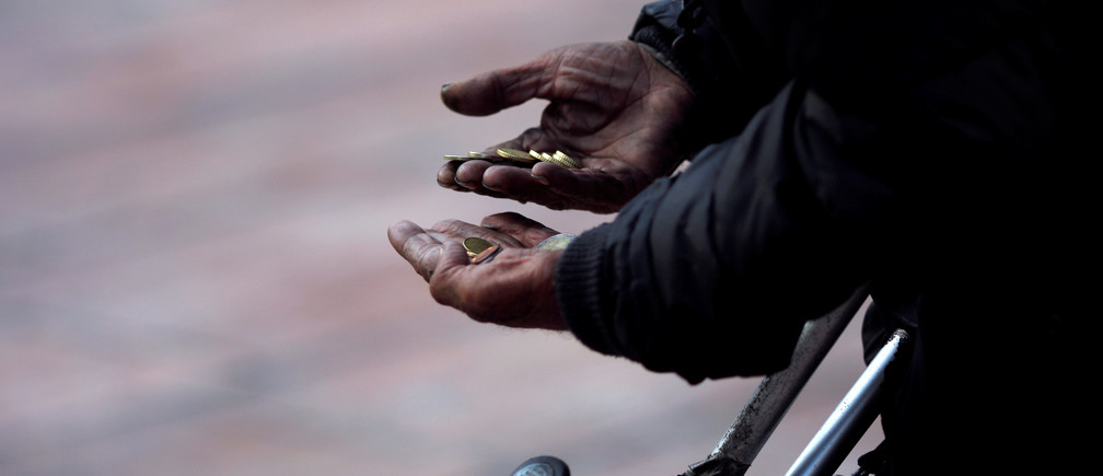 A beggar counts coins as he asks for alms during the International Day for the Eradication of Poverty in downtown Malaga, Spain October 17, 2016. REUTERS/Jon Nazca - D1BEUHNXZZAA