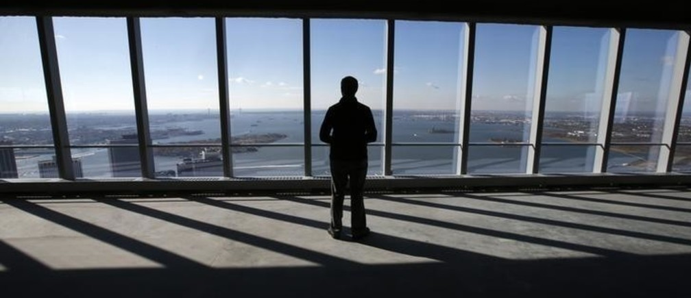A man looks out at New York harbor from the 68th floor of the soon to be opened 4 World Trade Center tower in New York, November 8, 2013. 4 World Trade center sits at the south east corner of the World Trade Center site and will be the second tower to open on the site since the 2001 attacks on the World Trade Center.  REUTERS/Mike Segar    (UNITED STATES - Tags: BUSINESS CITYSCAPE)