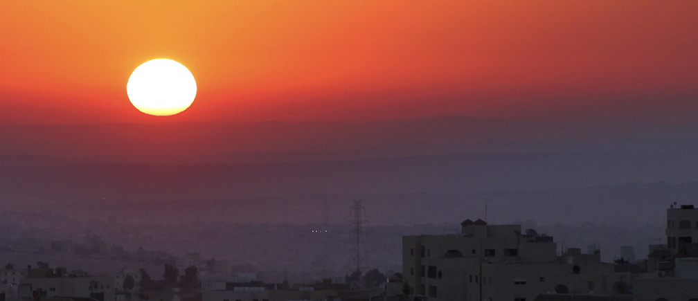 The sun rises on the first day of Eid al-Fitr in Amman August 19, 2012. Eid-al-Fitr marks the end of Ramadan, the holiest month on the Islamic calendar.  REUTERS/Muhammad Hamed (JORDAN - Tags: CITYSPACE ENVIRONMENT RELIGION) - GM1E88J1APD01