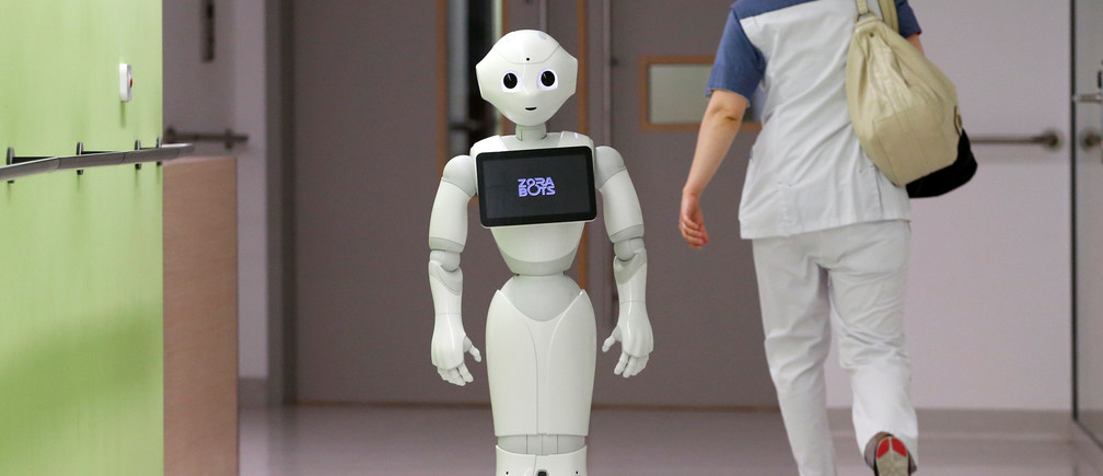 "A nurse walks by new recruit ""Pepper"" the robot, a humanoid robot designed to welcome and take care of visitors and patients, at AZ Damiaan hospital in Ostend, Belgium June 16, 2016. REUTERS/Francois Lenoir - D1AETKGAYIAA"