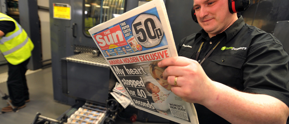 A pressman reads one of the first copies of the new Sun on Sunday newspaper to roll off the presses at the News Printers, in Broxbourne, England February 25, 2012. Rupert Murdoch bid to grab back the huge audience his News Corp lost when it closed Britain's best-selling News of the World over a phone-hacking scandal with a new Sunday edition of his Sun tabloid filled with gossip, girls and celebrities. Picture taken February 25, 2012.   REUTERS/John Stillwell/POOL  (BRITAIN - Tags: MEDIA BUSINESS) - RTR2YJ3L