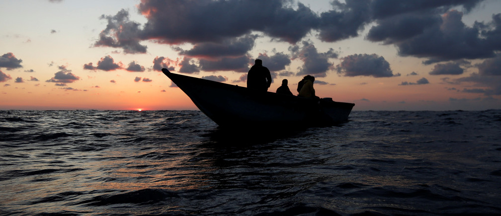 Libyan migrants on a wooden boat await rescue by the migrant search and rescue vessel MV Seefuchs of the German NGO Sea-Eye in the search and rescue zone some fifty nautical miles north of the Tunisian-Libyan land border, September 30, 2017. REUTERS/Darrin Zammit Lupi - RC1AED6D7160