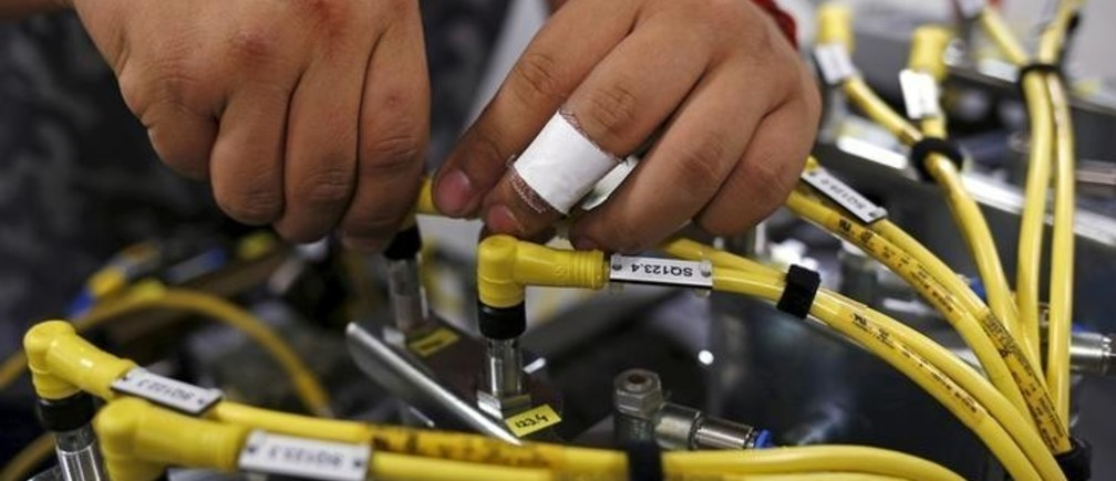 Christian Reyes works on some wiring at Felsomat in the Chicago suburb of Schaumburg, Illinois, United States, May 13, 2015. Christian Reyes, 18, with a budding interest in electronics, said neither he nor his Mexican-born parents ever imagined he would veer towards manufacturing. On the recommendation of a high school teacher, Reyes took an internship at Felsomat in 2014 during his senior year. Felsomat hired Reyes after graduation and he is now working toward a three-year degree in manufacturing at Harper College, a community college that resuscitated a dormant manufacturing course in 2012 at the urging of local companies. The future of manufacturing in the U.S. will largely be shaped by the strength of the U.S. dollar, energy costs and the outcome of trade deals such as the Trans-Pacific Partnership. But companies face a human challenge too - how to recruit young Americans to replace millions of Baby Boom-generation employees retiring over the next decade. To match Feature ECONOMY-MANUFACTURERS/RECRUITING         Picture taken May 13, 2015. REUTERS/Jim Young