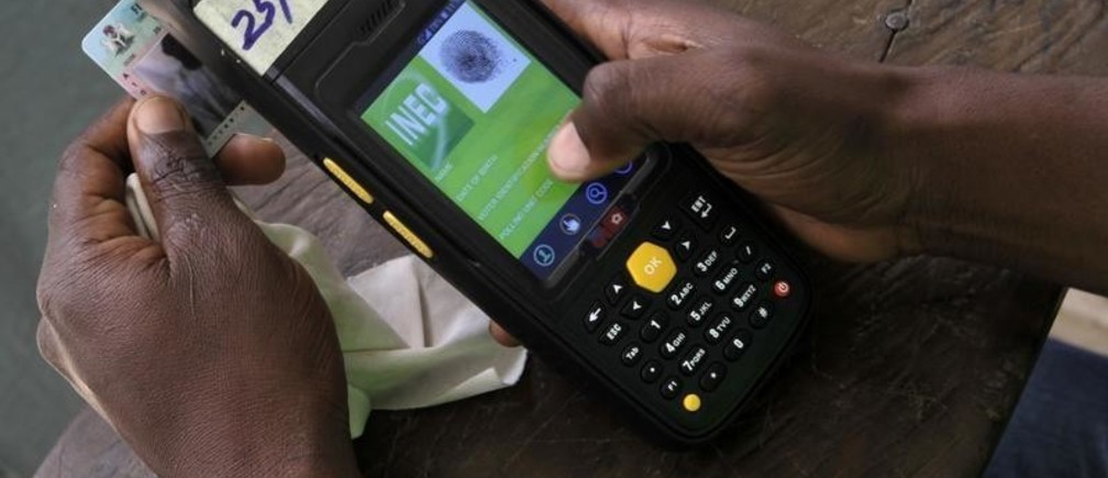 An Independent National Electoral Commmission (INEC) worker checks the validity of a voter's card during a mock accreditation execise ahead of the March 28 presidential election at Garaku West ward in Lafia, March 7, 2015. Picture taken March 7, 2015.  REUTERS/Afolabi Sotunde (NIGERIA - Tags: POLITICS ELECTIONS) - GM1EB3A03XX01