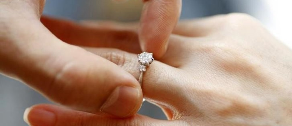 A man puts an engagement ring on a woman's finger during a photo opportunity at a jewellery store in Tokyo June 2, 2009. Japanese men are increasingly spending less on diamond engagement rings or not buying them at all, a reflection of the country's sluggish economy and changing views on courtship and marriage.