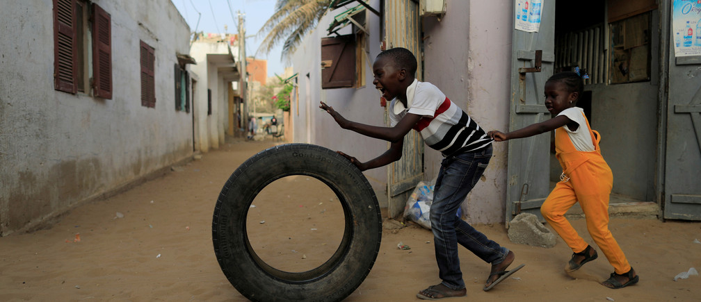 Children play with a tire, amid the outbreak of the coronavirus disease (COVID-19), in Yoff neighbourhood of Dakar, Senegal June 24, 2020. REUTERS/Zohra Bensemra     TPX IMAGES OF THE DAY - RC2XFH99Q9PE