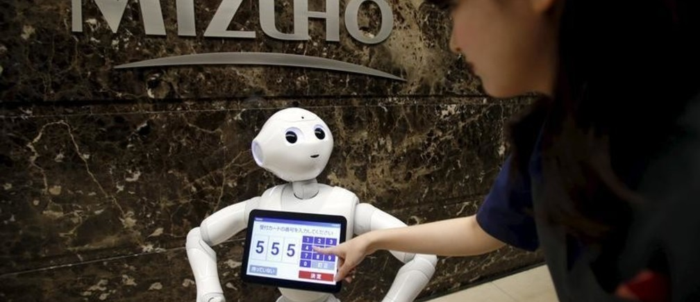 "SoftBank's human-like robot named ""Pepper"" demonstrates how to welcome a customer as a concierge during a photo opportunities at an entrance of Mizuho Financial Group's Mizuho bank branch in Tokyo, Japan, July 17, 2015. Pepper starts working as a concierge of the bank to welcome customers. REUTERS/Yuya Shino - GF10000161538"