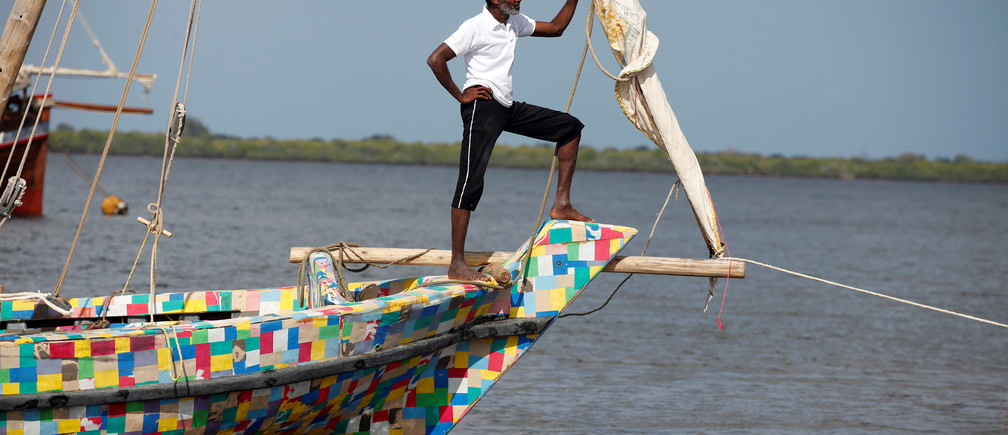 A man stands on the front of Flipflopi the first dhow boat made entirely of recycled plastic during its launch ceremony on the island of Lamu, Kenya, September 15, 2018. REUTERS/Baz Ratner - RC185C961100
